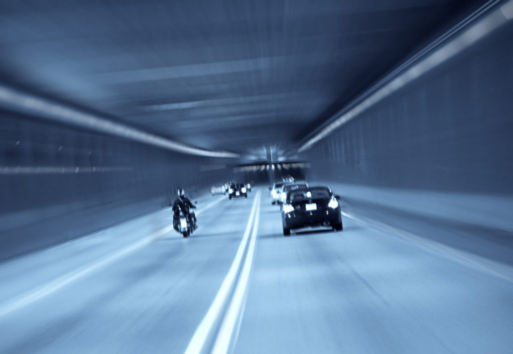 Motorcycle is running in a expressway tunnel with cars aside