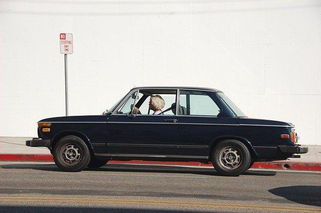 Senior lady driving a vintage car