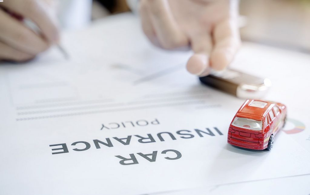 Car insurance policy with red car toy and blur image of man hand